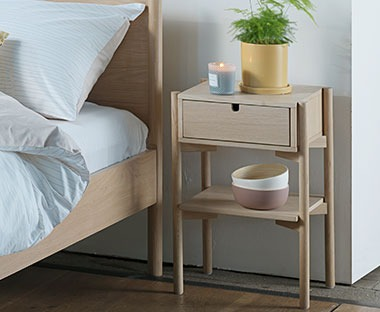 An oak bedside table with drawer and shelf