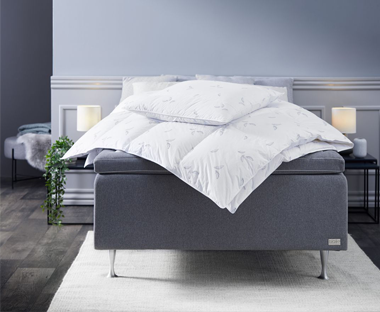 duvet cover on grey bed frame with two warm glowing bedside lights