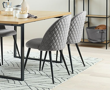 velvet Quilted back dining chairs in grey with black chair legs