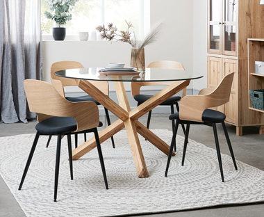 Scandinavian design wooden dining chairs with ergonomic seat design and black metal legs placed around round glass dining table with chunky wooden legs