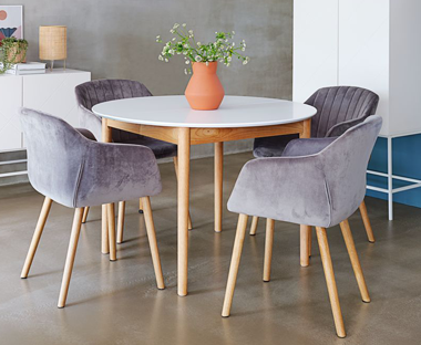 Contemporary round wooden table with white top and oak legs paired with grey upholstered velvet chairs with matching oak legs
