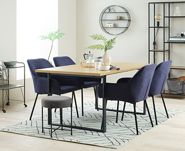 Metal frame wooden top table with dark blue upholstered dining chairs