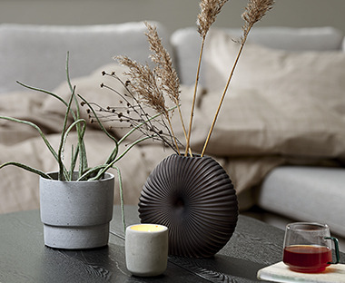 shell-like black vase with concrete plant pot and candle on coffee table in living room