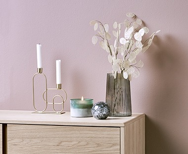 Grey glass vase and gold candlestick on an oak sideboard