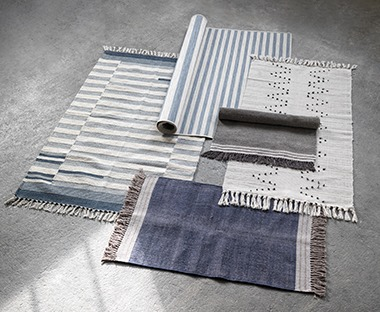 blue rugs with striped and patch design and fringing ends. Boho rug with dots and line design.