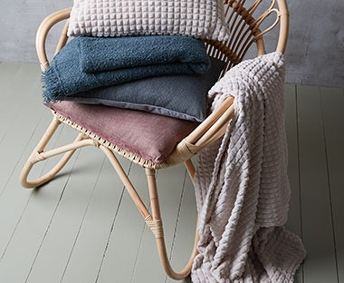 Blush pink and petrol blue throws draped over a wicker chair