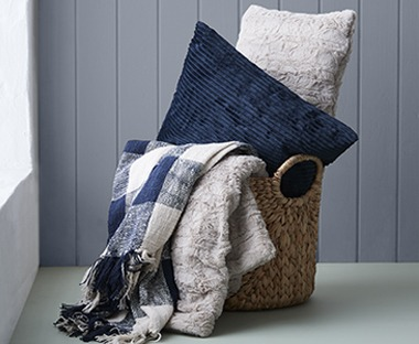 Blue and white checked design throw with tassel edges. Throws in basket with soft fluffy cushions
