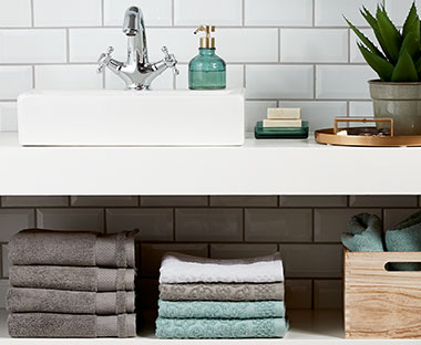 A modern bathroom plush grey towels and green glass bathroom acessories