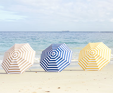 striped parasol in assorted colours on a beach