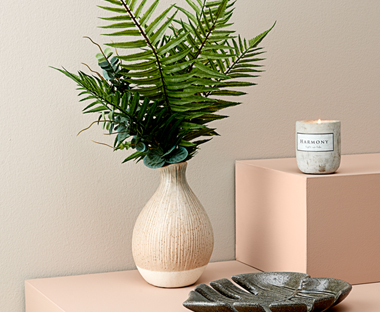Textured beige vase with artificial palm leaves