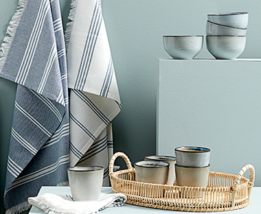 Blue bowls, mugs and tea towels on a wicker tray