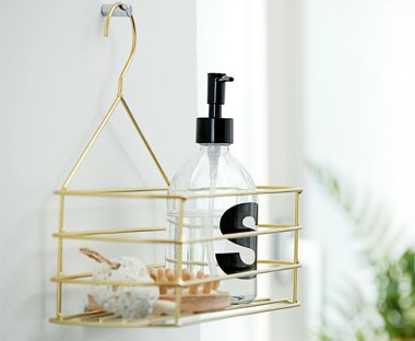 Plastic soap dispenser with golden metal shower storage