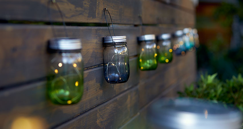 Green and blue lanterns hanging on garden fench