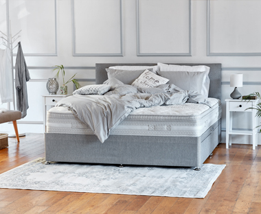 A spring mattress with grey headboard and divan base
