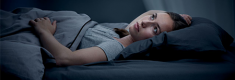Woman lay in bed with head on the pillow wide awake