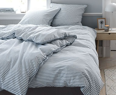 A nautical bedding set with white and blue stripes and blue piping