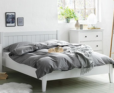 white wooden bed frame with headboard