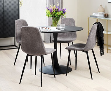 Round black dining table with grey corduroy dining chairs