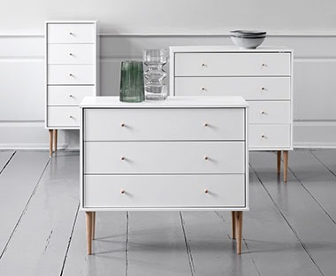 a collection of white chest of drawers with three, four and five drawers