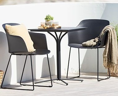 Black plastic garden chairs with black bistro table