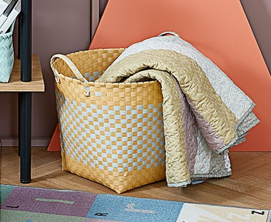 A colourful quilted blanket in childrens playroom in colourful yellow storage basket