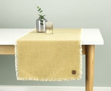A contemporary yellow table runner with fringe edging