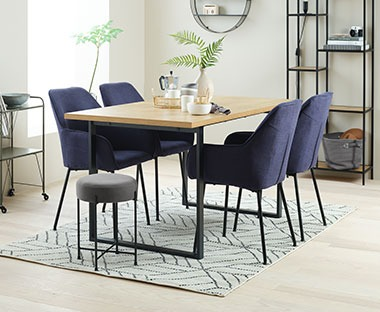 a modern dining set wooden table top and metal frame with dark blue upholstered dining chairs