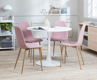 white round table with pink dining chairs with rose gold chair leg