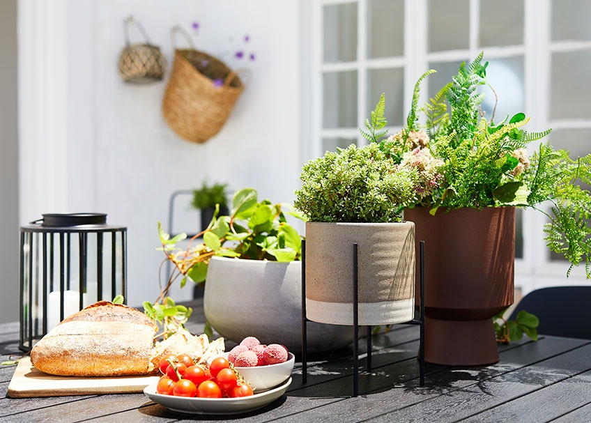 Ceramic plant pot, lantern and tray with bread and fruit on a garden table