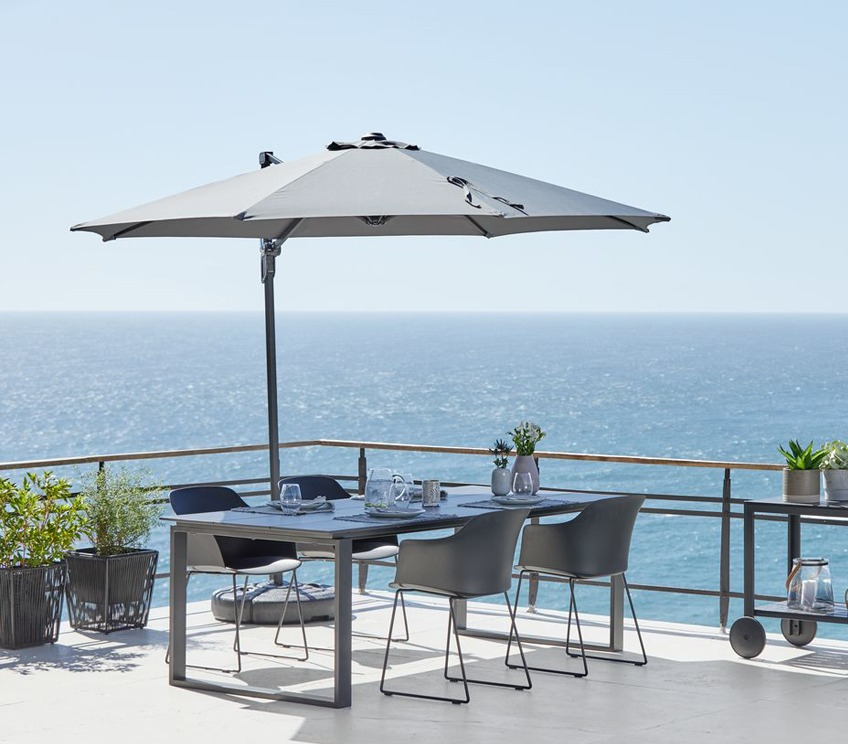 Hanging parasol casting shade over garden table and chairs set