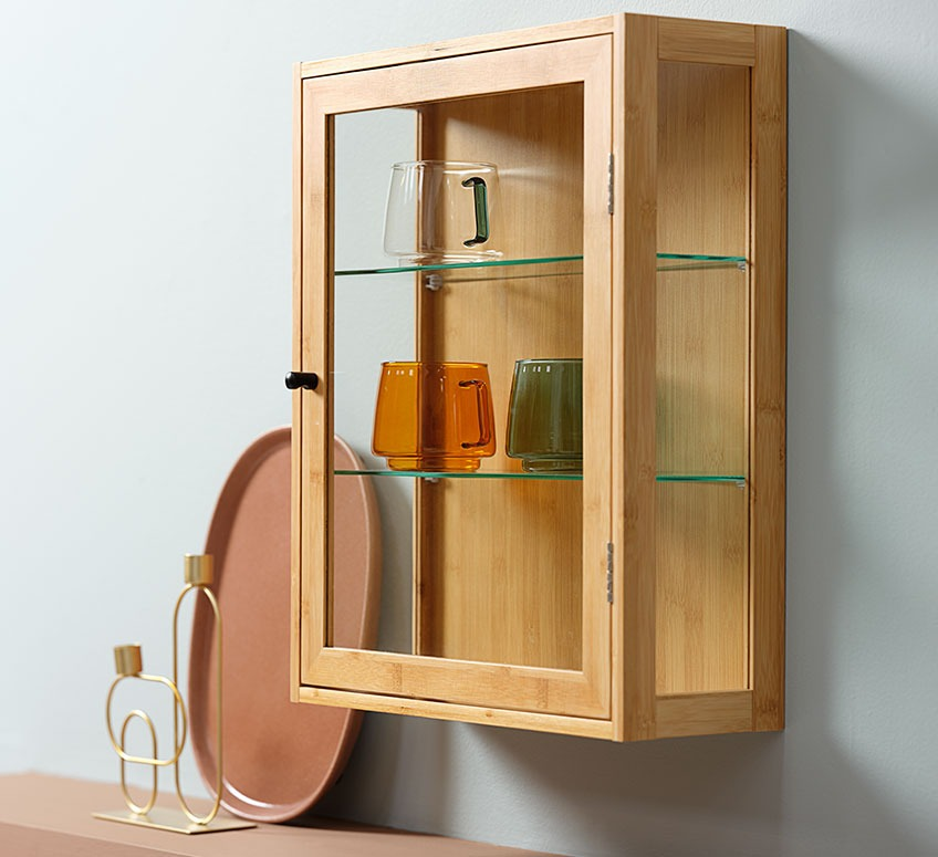 Small cabinet with hand-blown glass cups and candlestick and tray in the background