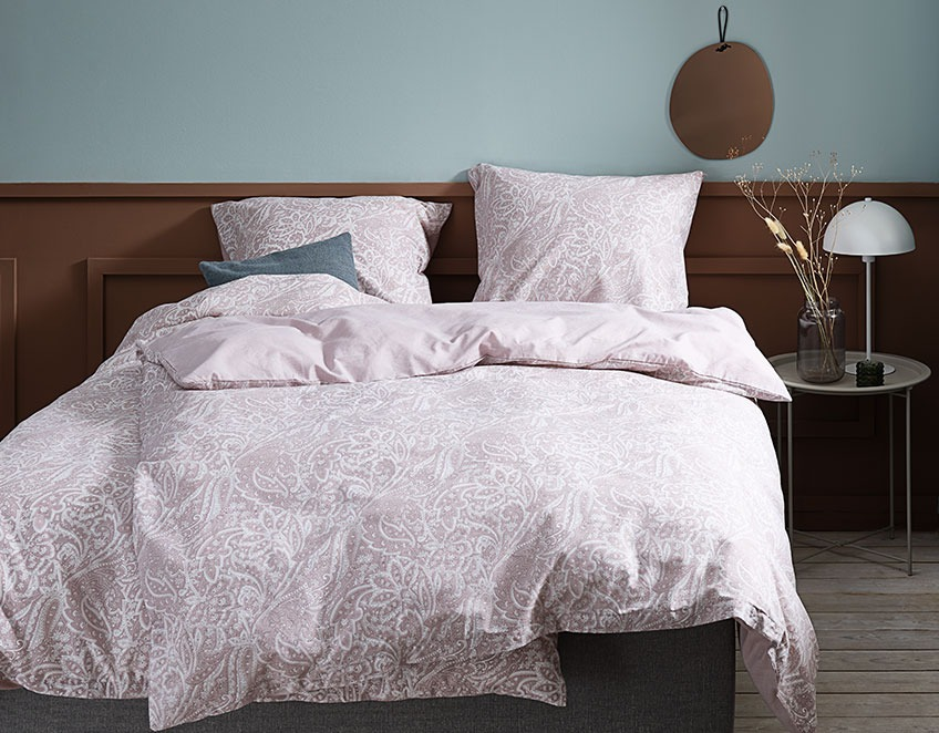 Pink duvet cover set with a paisley pattern in a rustic bedroom