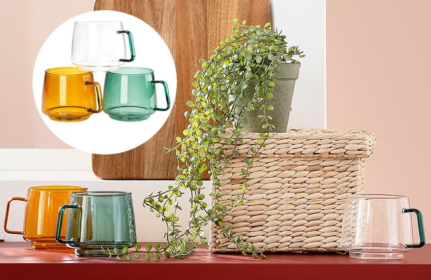 Transparent coffee cups in green, amber and clear on a table with a basket