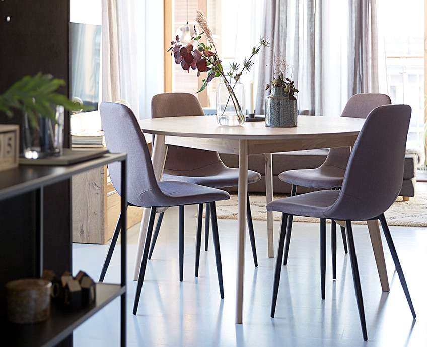 Grey dining chairs around round white dining table in modern apartment