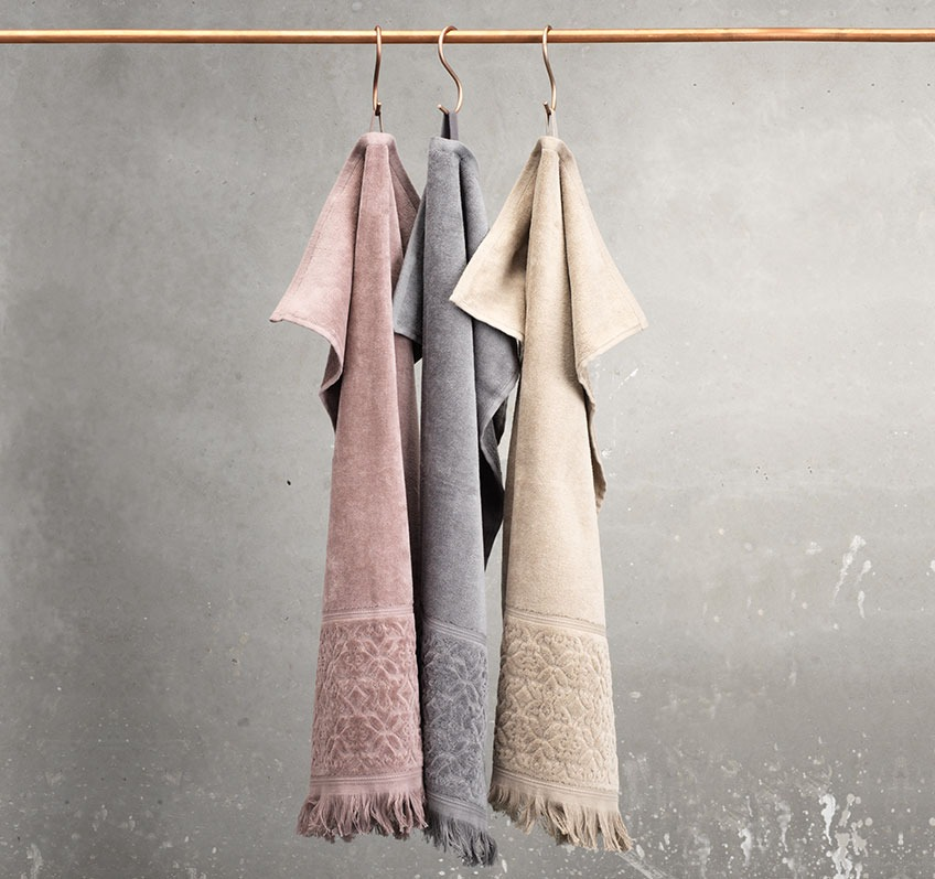 Taupe, sand and grey towel hanging from a rail