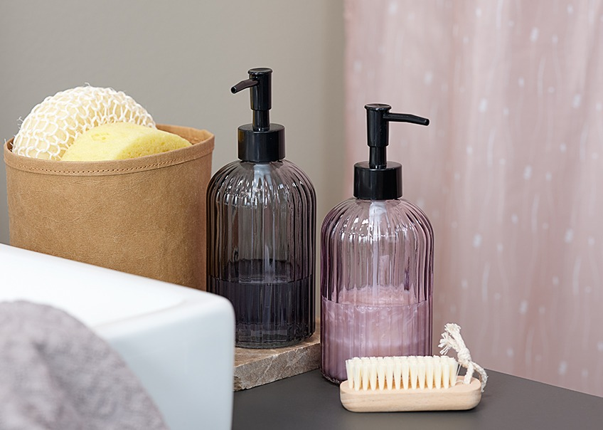 Glass soap dispensers in different colours, sponges and a nail brush