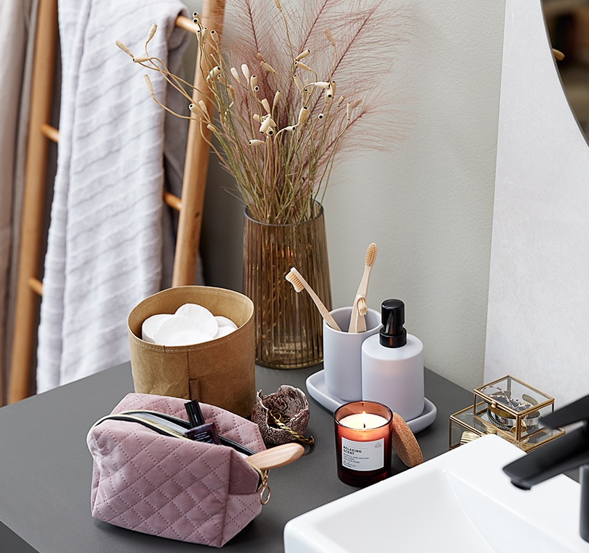Scented candle, bathroom set and toiletry bag as bathroom décor
