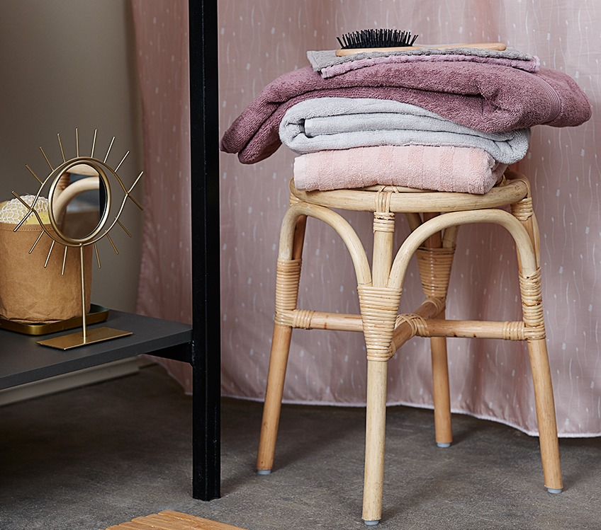 Towels stacked on a stool next to a decorative mirror