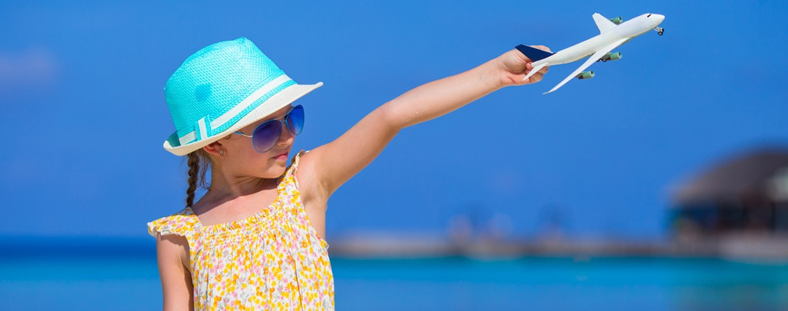 Girl holding toy airplane in the air