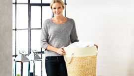 Woman with laundry basket filled with pillows
