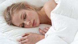 A woman sleeping under a duvet with head on a pillow