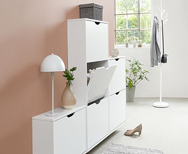 a series of white shoe storage racks with cupboards for discrete storage